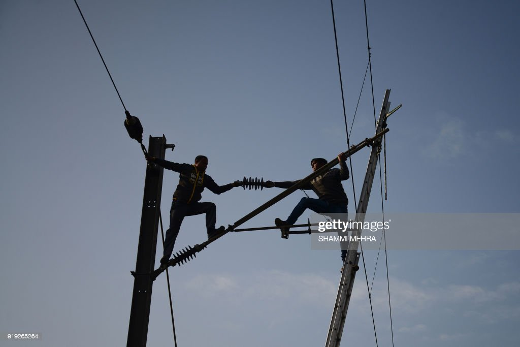 Indian Railways workers repair high voltage train power lines in Jalandhar on February 17 2018 / AFP PHOTO / Shammi MEHRA