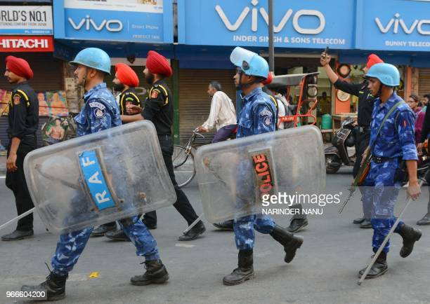 Indian Rapid Action Force personnel along with Punjab Police personnel patrol ahead of the 34th anniversary Operation Blue Star at a market in...