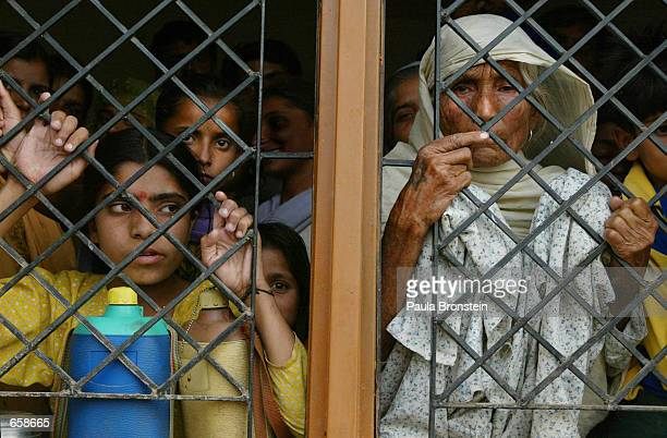 Indian refugees peek out from the window of a school turned migrant camp in RS Pura on June 6 2002 in Jammu the winter capital of the disputed region...