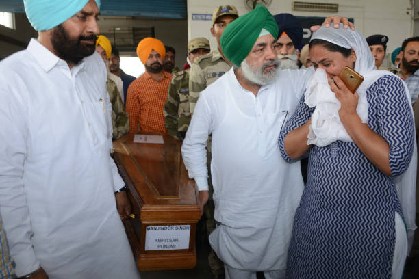 Indian relative Gurpinder Kaur cries near the coffin of her borther Manjinder Singh who was killed in Iraq at the International Airport in Amritsar...