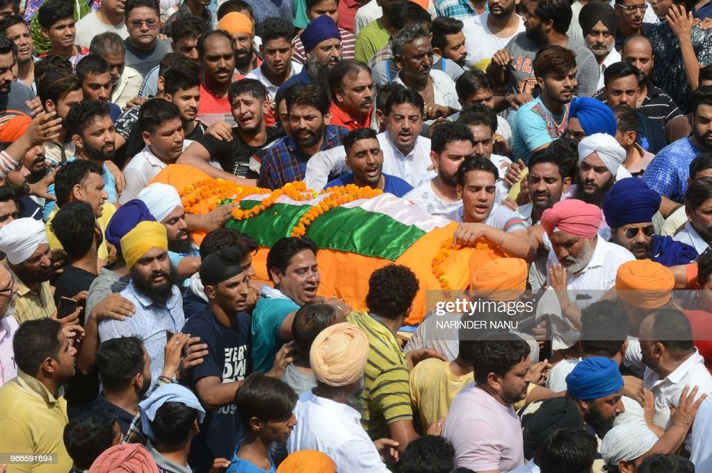 Indian Relatives and residents carry the body of slain Congress party councillor Gurdeep Singh Pehalwan during his cremation ceremony at Shivpuri...