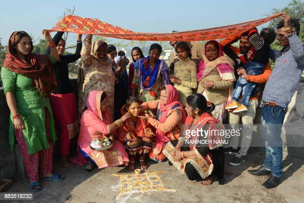 Indian relatives apply turmeric 'haldi' on the face of the bride Sharda as they celebrate the Vatna ceremony during a wedding in Amritsar on November...