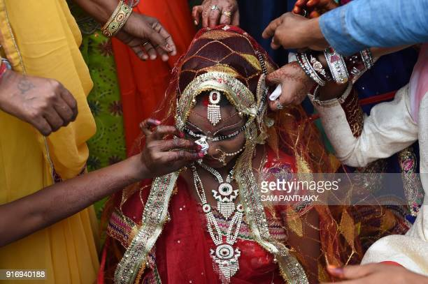 TOPSHOT Indian relatives help a bride to wear a necklace during a mass wedding for members of the Adivasi Bhil tribal community in Ahmedabad on...