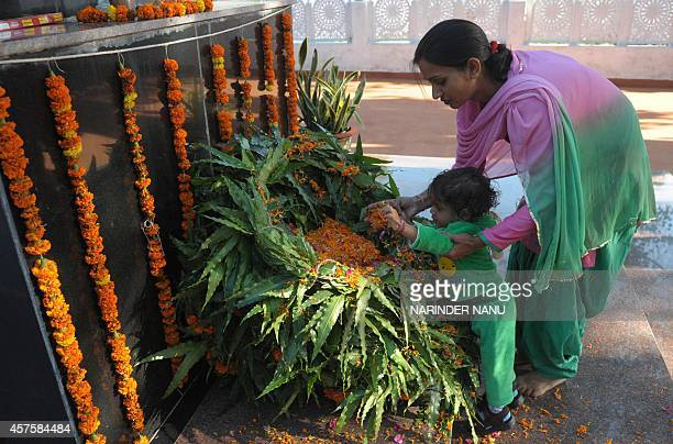 Indian relatives of a deceased Punjab police official leave flowers at a memorial during an event to mark Police Commemoration Day in Amritsar on...