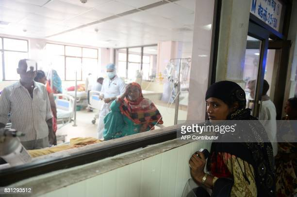 Indian relatives of patients wait outside the encephalitis ward at the Baba Raghav Das Hospital in Gorakhpur in the northern Indian state of Uttar...