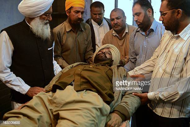 Indian relatives of Punjab Police assistant sub inspector Kulbir Singh carry his body at a hospital in Tarn Taran district about 25 kms from Amritsar...