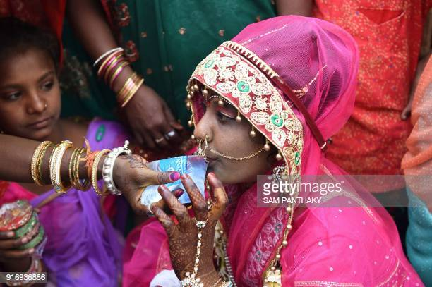 Indian relatives offer water to a bride during a mass wedding for members of the Adivasi Bhil tribal community in Ahmedabad on February 11 2018 Some...
