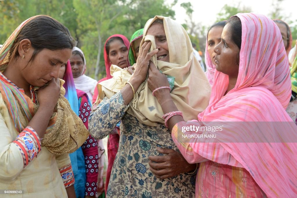 Indian relatives Seema and her mother inlaw Jeeto cry during the cremation ceremony for her husband Sonu who was killed in Iraq in the village of...