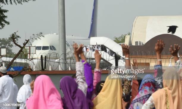 Indian relatives wave as Hajj pilgrims board an Airbus A330 flight bound for Saudi Arabia at Sardar Vallabhbhai Patel International Airport in...