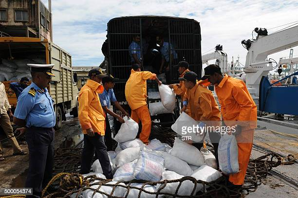 Indian relief workers load supplies for flood victims in Chennai on December 5 2015 Thousands of rescuers are racing to evacuate victims of the Tamil...