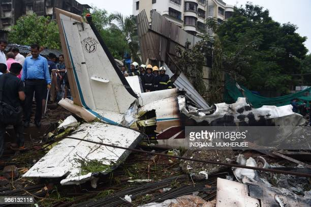 Indian rescue firemen and aviation officials gather around the wreckage of a small plane that crashed into a construction site killing five people in...