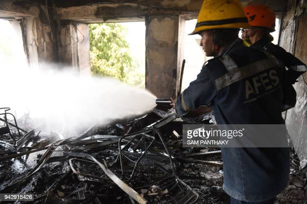 Indian rescue personnel of the Ahmedabad Fire Emergency Services use a high velocity water mist spray nozzle device to control a fire at a corporate...