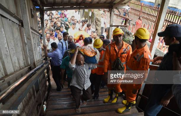Indian rescue personnel walk through the scene of a stampede on a railway bridge in Mumbai on September 29 2017 Commuters stampeded on a Mumbai...