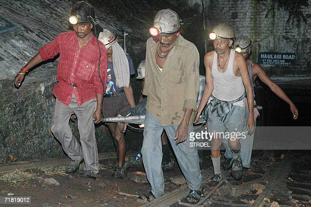 Indian rescue team members carry the dead body of a miner out of a seam at the Bhatdih colliery, two days after a massive explosion trapped miners in...