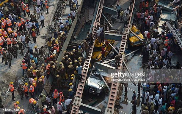Indian rescue workers and volunteers try to free people trapped under the wreckage of a collapsed flyover bridge in Kolkata on March 31 2016 At least...