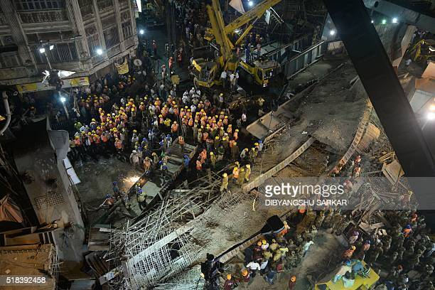 Indian rescue workers and volunteers try to free people trapped under the wreckage of a collapsed flyover in Kolkata on March 31 2016 Hundreds of...