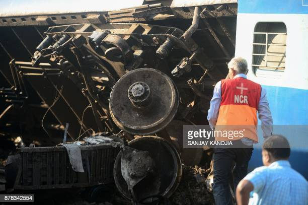 Indian rescue workers assess the derailed coaches of an Indian express train are pictured near Manikpur railway station in Uttar Pradesh on November...