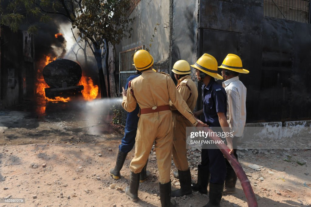 Indian rescue workers from the Ahmedabad Fire and Emergency Services along with trainee firemen of the Nagpur-based, National Fire Service College fight a blaze in the Vatwa area of Ahmedabad on November 30, 2013. A major fire broke out in a storage facility when a motor tanker containing solvent chemical caught fire with the cause of the fire under investigation. Hazardous godowns of chemicals in the residential localities are a cause of concern. AFP PHOTO / Sam PANTHAKY