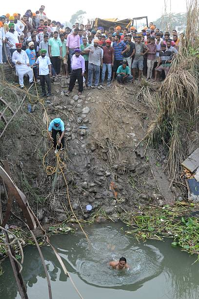 Indian rescue workers search for bodies of missing schoolchildren after their bus fell into a drainage area at Muhawa village 35 km from Amritsar...