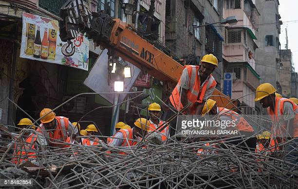 Indian rescue workers try to free people trapped under the wreckage of a collapsed flyover bridge in Kolkata on April 1 2016 Emergency workers in...