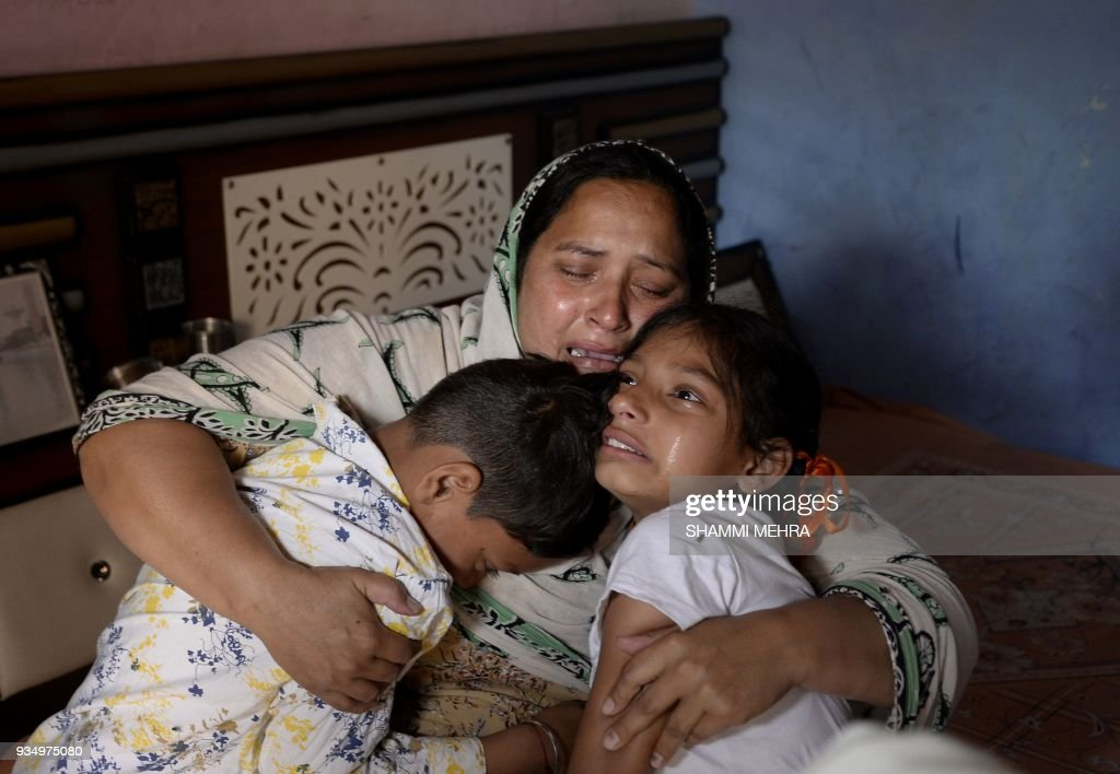 Indian resident Amandeep Kaur holds her daughter Sanjna and son Harsh as they react to the confirmation of the death of her husband Kulwinder Singh...