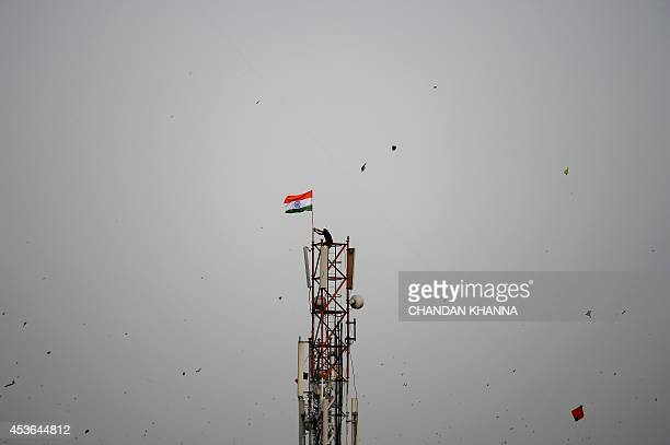 A Indian resident climbs to the top of a telephone tower to hoist the national flag during Independence Day in New Delhi on August 15 2014 India's...