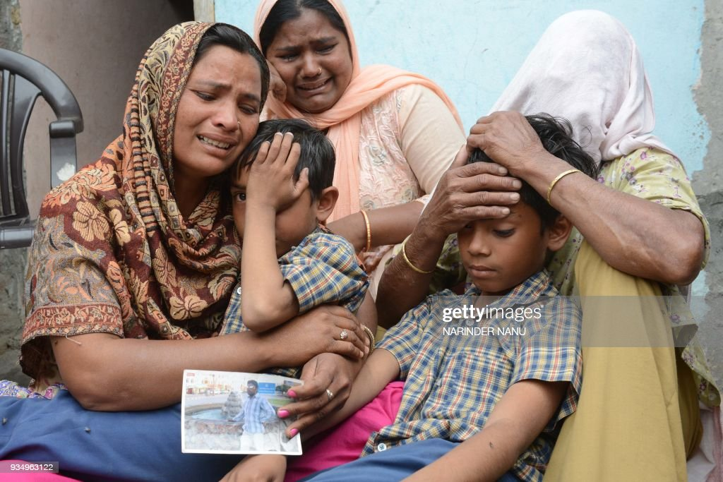 TOPSHOT Indian resident Seema her sons Karan and Arjun and her mother inlaw Jeeto react following confirmation by External Affairs minister Sushma...