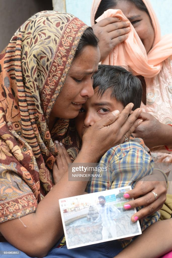 Indian resident Seema holds her son Arjun as she reacts following confirmation by External Affairs minister Sushma Swaraj that her husband Sonu had...