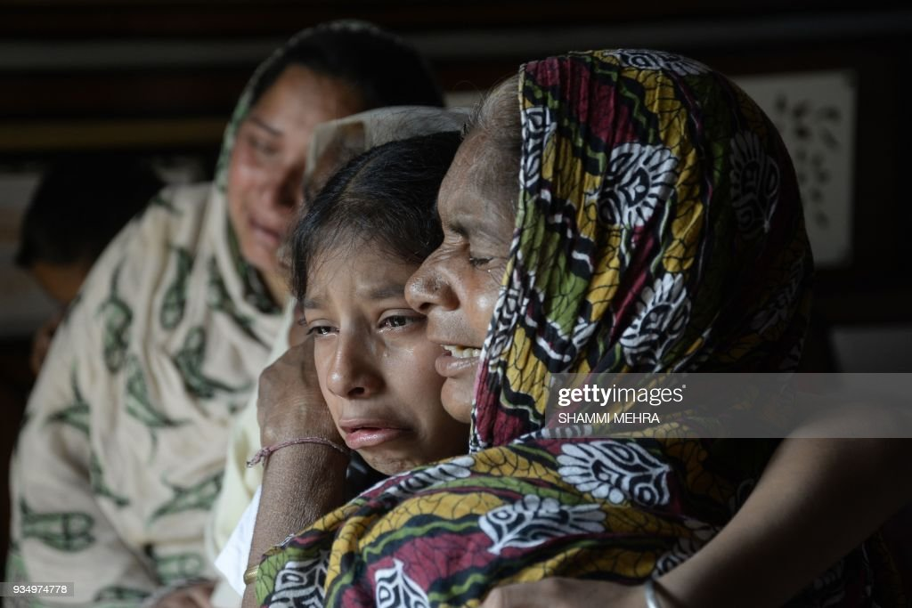 TOPSHOT Indian resident Shimbo holds her granddaughter Sanjna as they react to the confirmation of the death of her son Kulwinder Singh in Khan Ke...