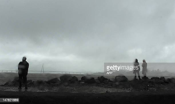 Indian residents are seen through a vehicle windscreen as they stand near the sea front during rain showers in Mumbai on July 4 2012 India's...