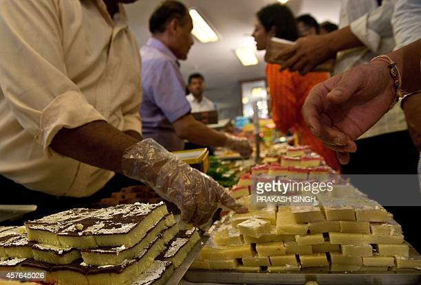 Indian residents buy sweets ahead of the forthcoming Diwali festival in New Delhi on October 22 2014 AFP PHOTO / PRAKASH SINGH