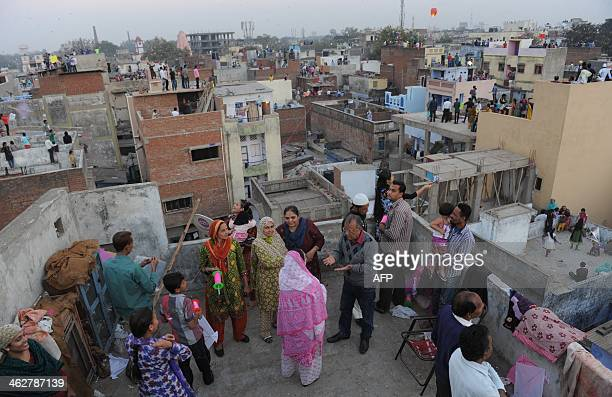Indian residents celebrate Uttarayan or a kite flying festival in the Walled City of Ahmedabad on January 15 2014 'Uttarayan' which falls on January...