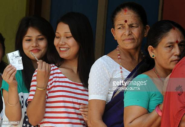 Indian residents check their voting identity cards as they queue at a polling station in Siliguri on April 17 during national elections India is...