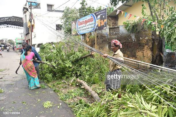Indian residents clear away fallen trees near the train station in Nagapattinam in India's southern Tamil Nadu state on November 16 after a cyclone...