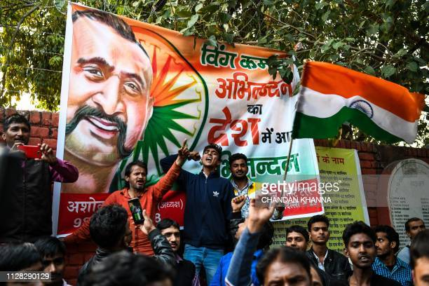 Indian residents dance shout slogans and wave the national flag at a central market in New Delhi on March 1 as they wait for the return of an Indian...