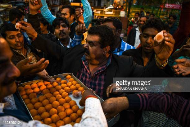 Indian residents distribute sweets dance shout slogans and wave the national flag at a central market in New Delhi on March 1 as they wait for the...