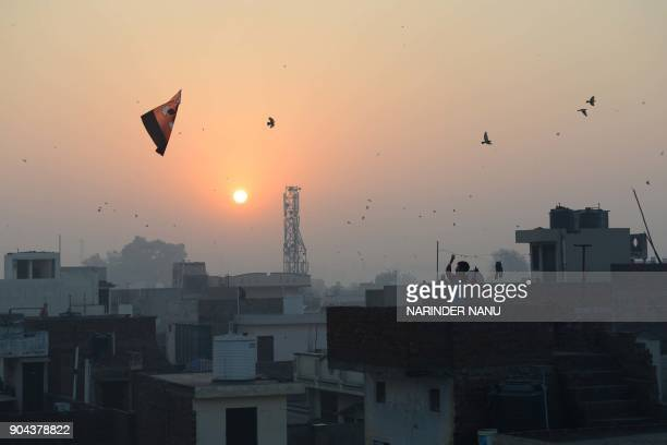 Indian residents fly kites during celebrations for the Lohri festival in Amritsar on January 13 2018 The Lohri harvest festival which falls on...