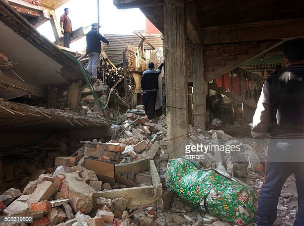 Indian residents gather in the wreckage of a building in Imphal on January 4 after a strong 67 magnitude earthquake struck northeast India near the...