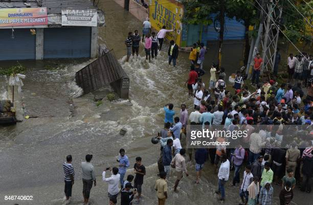 Indian residents gather on a flooded street following heavy rains in Hyderabad on September 14 2017 Heavy rains brought flooding to low lying areas...