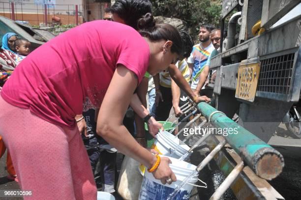 Indian residents gather to collect drinking water with buckets from a water tanker following water shortages in Shimla in the northern state of...