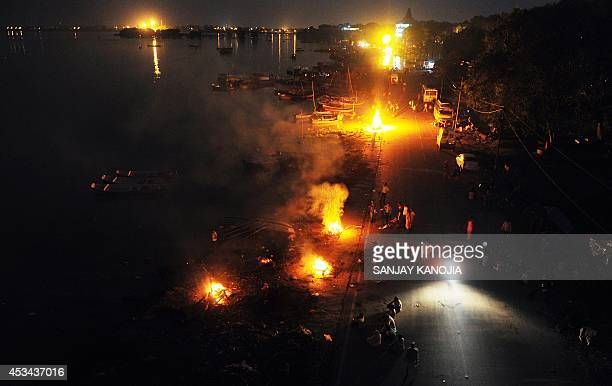 Indian residents hold cremations for the dead along a roadside following heavy flooding at Daraganj ghat near Sangam in Allahabad on August 10 2014...