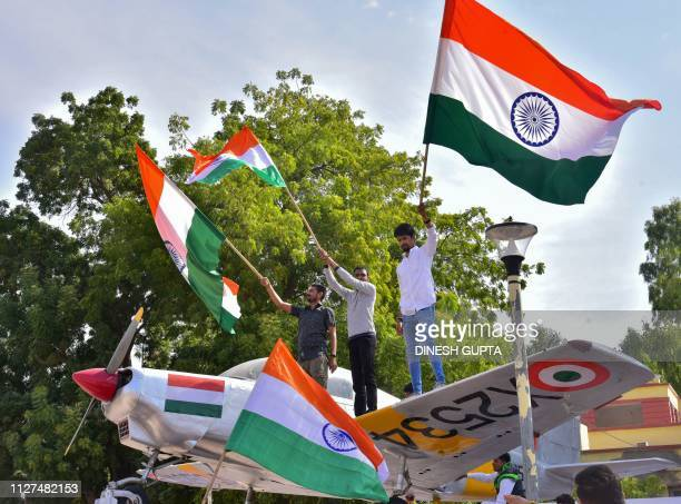 Indian residents hold flags on a model of a military plane to celebrate the Indian Air Force strike launched on a JaisheMohammad camp at Balakot in...