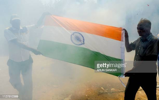 Indian residents hold the national flag through a cloud of smoke as they participate in a demonstration to support Indian armed forces in Chennai on...