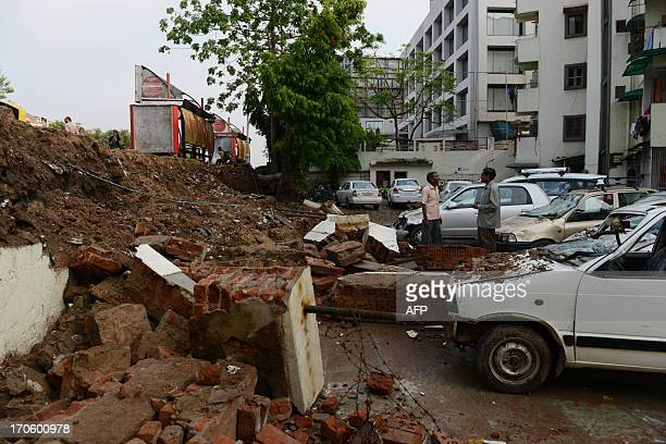 Indian residents interact near damaged parked cars in Ahmedabad on June 15 2013 A wall at a residential complex collapsed during heavy rains the...