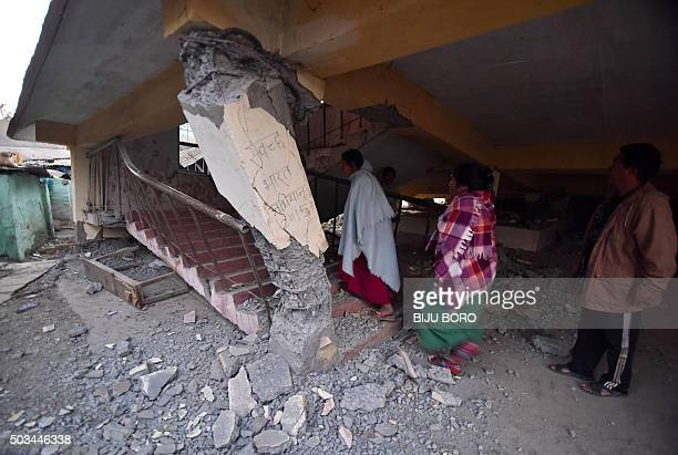 TOPSHOT Indian residents look at a damaged building in Saikul some 58 km from Imphal on January 5 2016 following a 67 magnitude earthquake At least...