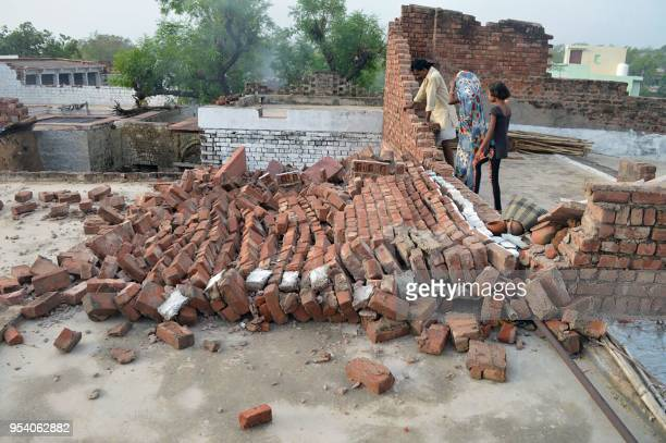 Indian residents look at a wall damaged by high winds during a major dust storm in Agra district in northern India's Uttar Pradesh state on May 3...