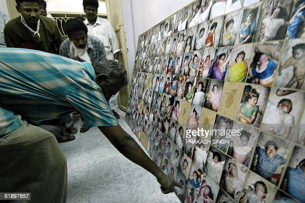 Indian residents look at pictures of dead people on display for identification at a church in Velankani some 365 km south of Madras 28 December 2004...