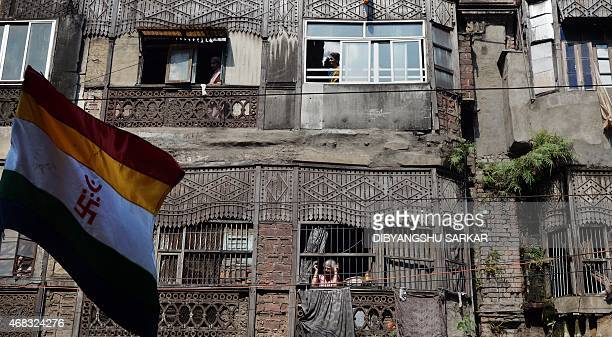 Indian residents look out from their windows to see a religious rally organised on the occasion of Mahavir Jayanti in Kolkata on April 2 2015 The...
