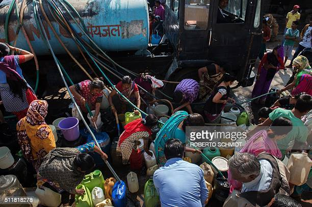TOPSHOT Indian residents of the eastern New Delhi neighborhood of Sanjay Camp use hoses to fill water jugs from a water distribution truck which...