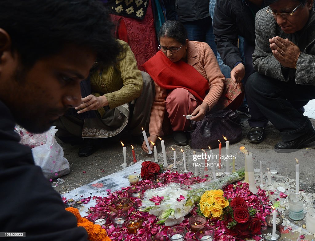 Indian residents pray in front of candles and flowers in New Delhi on December 30, 2012, after the cremation ceremony for a gangrape victim. The victim of a gang-rape and murder which triggered an outpouring of grief and anger across India was cremated at a private ceremony, hours after her body was flown home from Singapore. A student of 23-year-old, the focus of nationwide protests since she was brutally attacked on a bus in New Delhi two weeks ago, was cremated away from the public glare at the request of her traumatised parents.